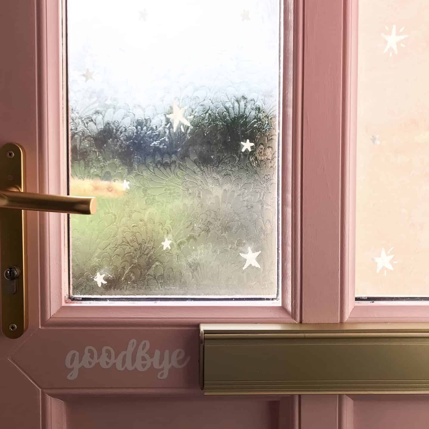 Hand drawn chalk pen stars on a pink front door window