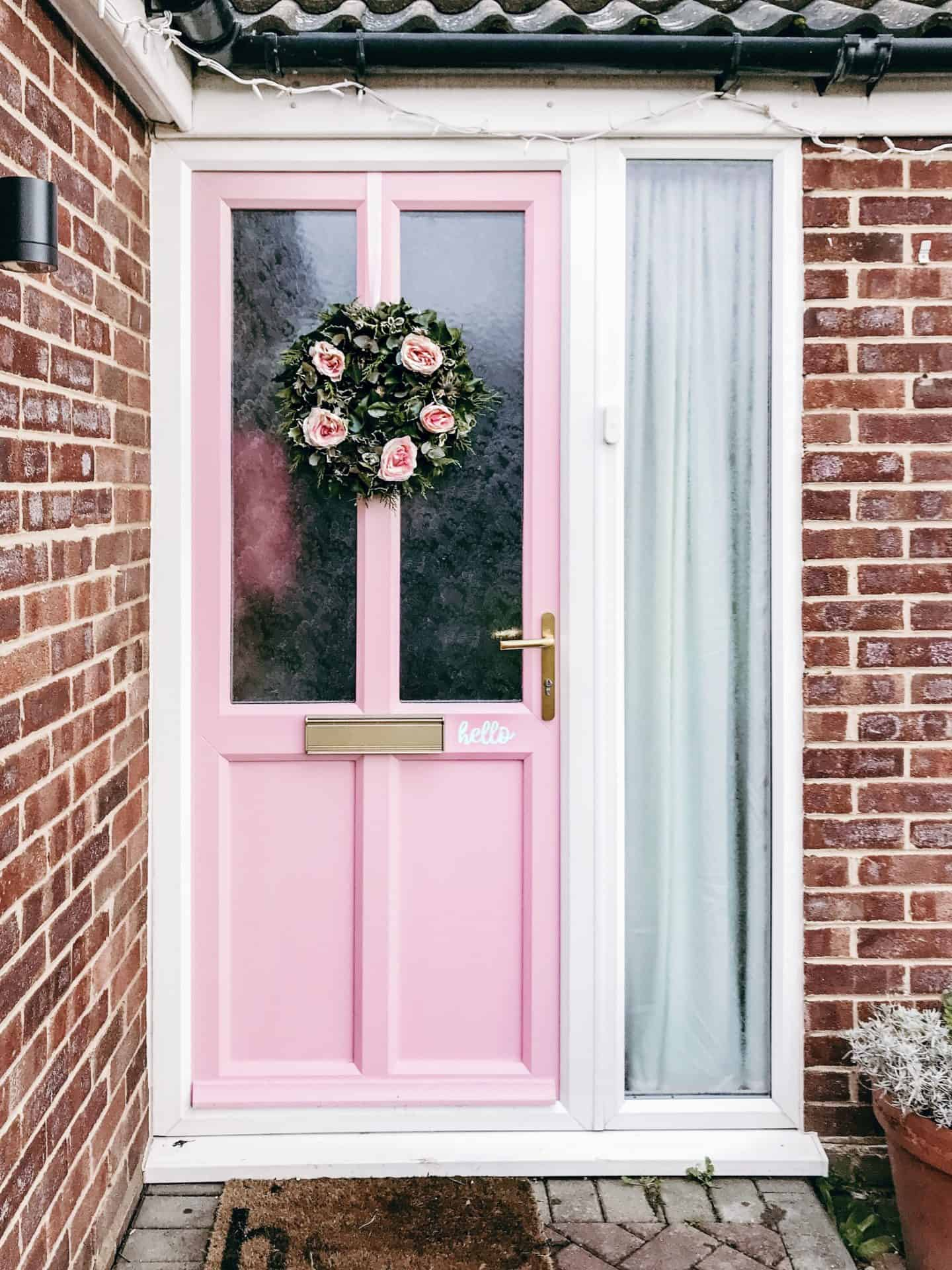 Pink front door with green and pink hand made Christmas wreath