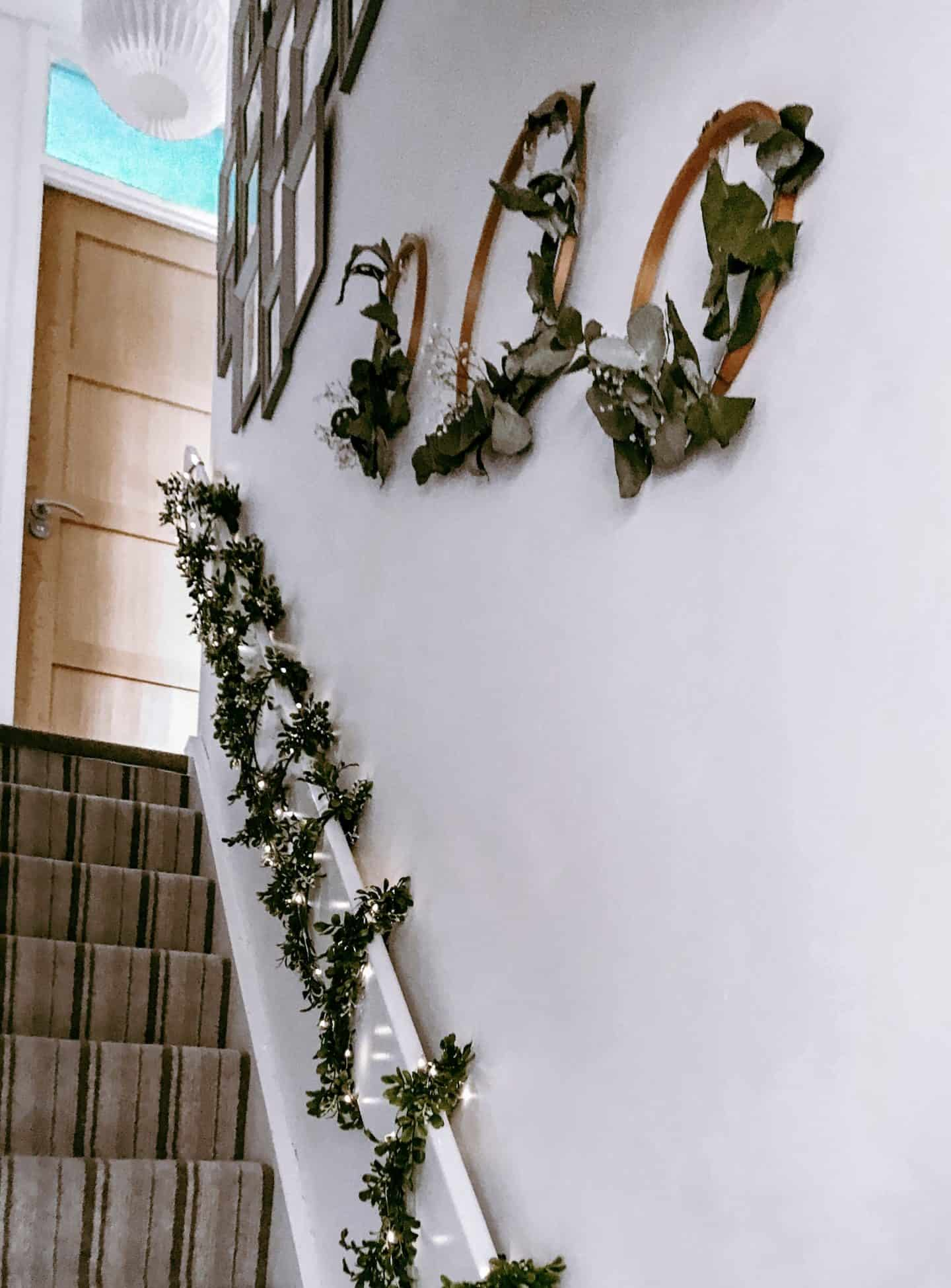 Stairs with fairy lights and garlands and hoop Christmas wreaths