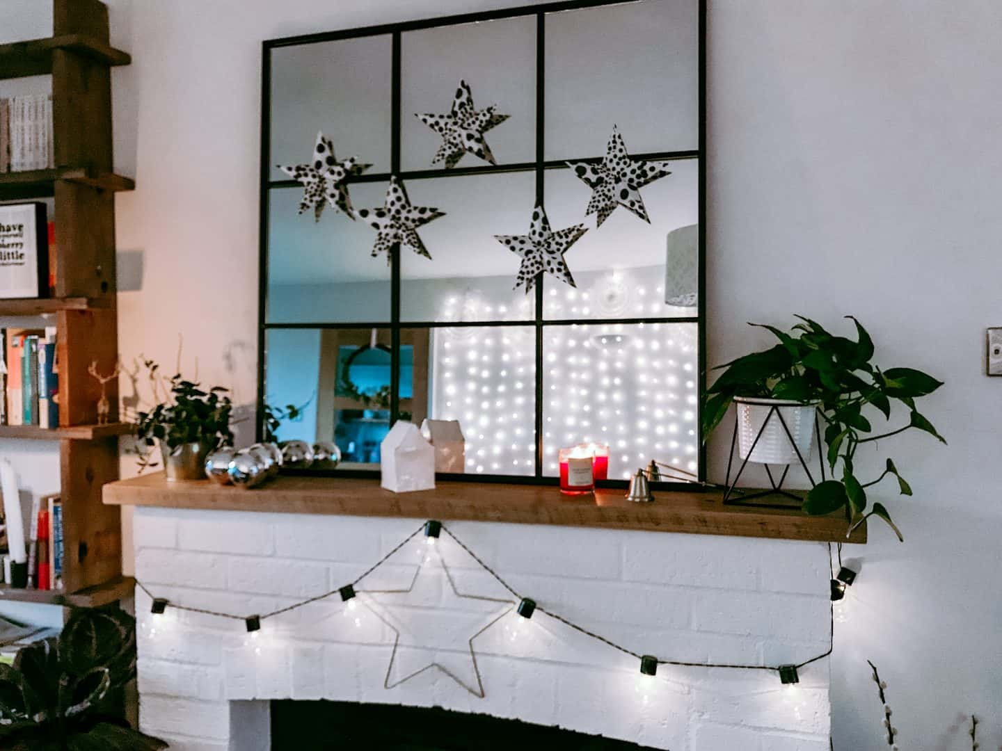 White mantlepiece decorated for Christmas with lights and origami stars