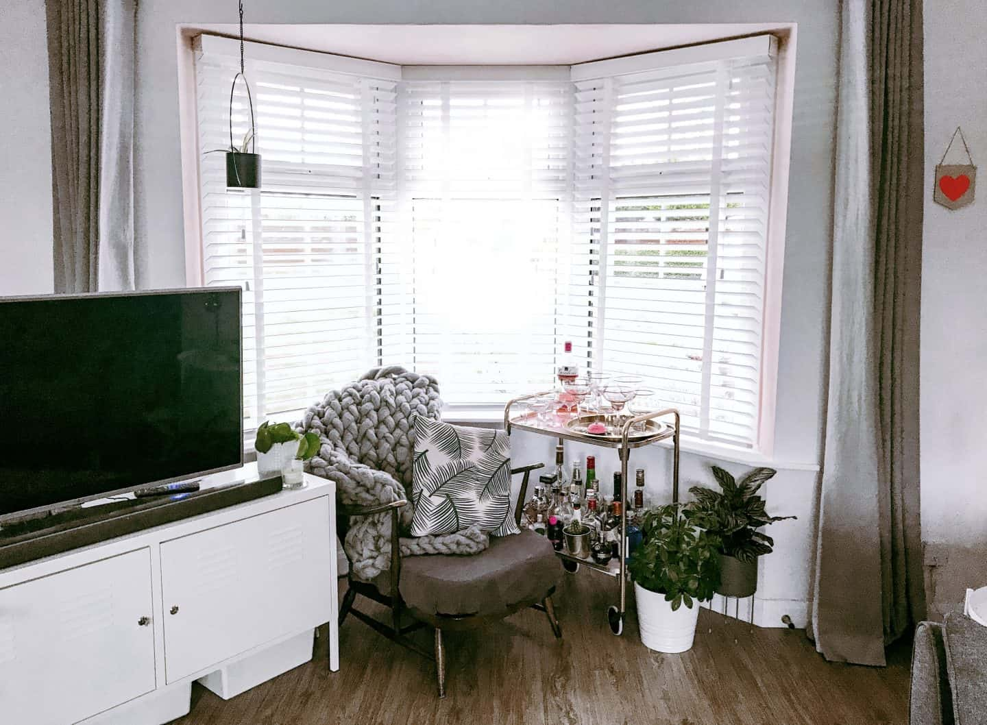 Bay window with white wooden shutter-style blinds with tapes, a vintage Ercol armchair and a gold drinks trolley