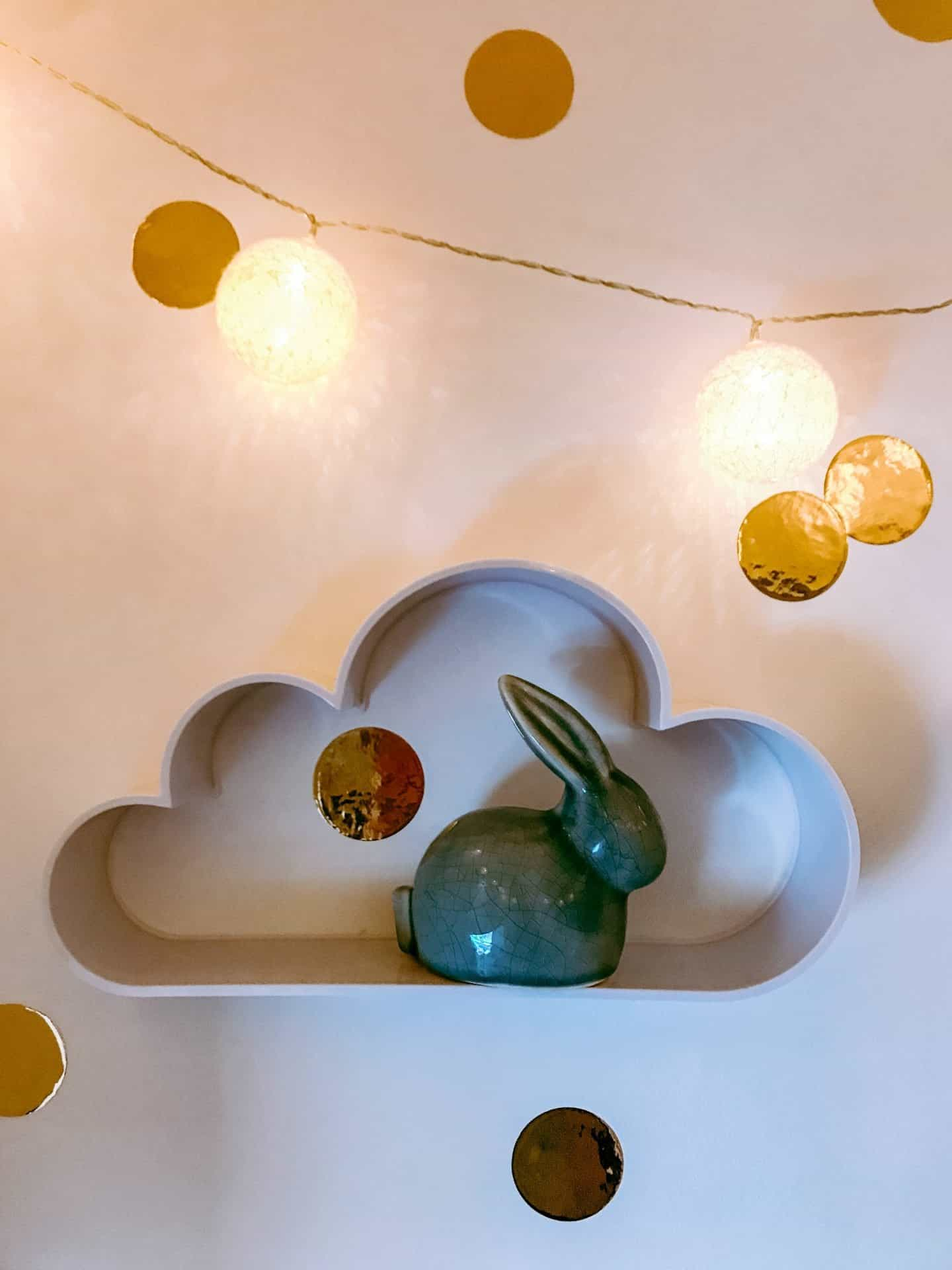 Cloud shelf with a blue pottery rabbit, gold confetti wall stickers and fairy lights