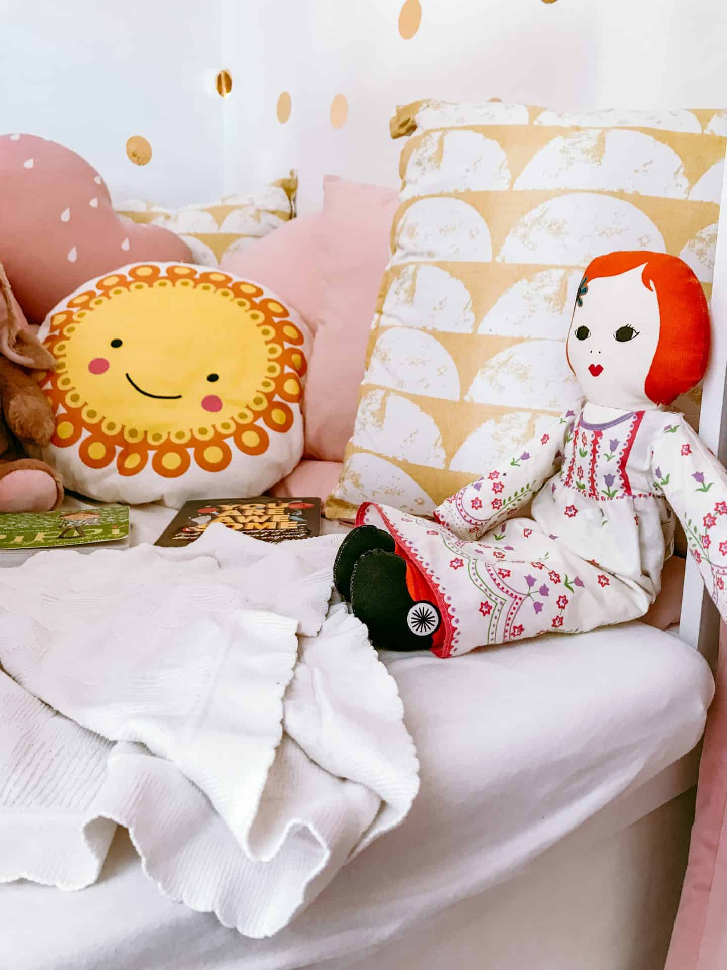 Cosy kids' reading nook with pink and yellow cushions and a Clothkits doll