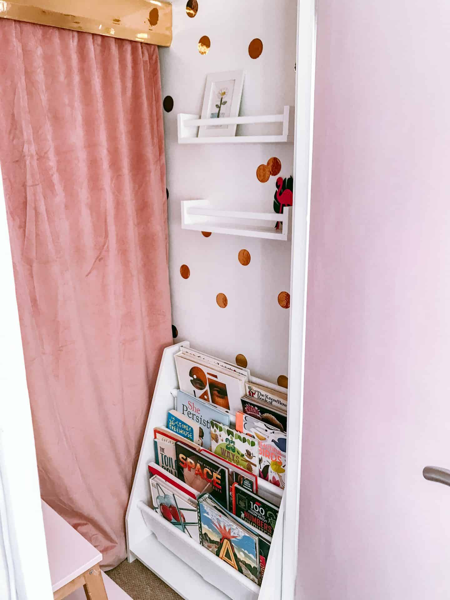 Cupboard made into a kids' den with white shelves and a book case and a velvet curtain