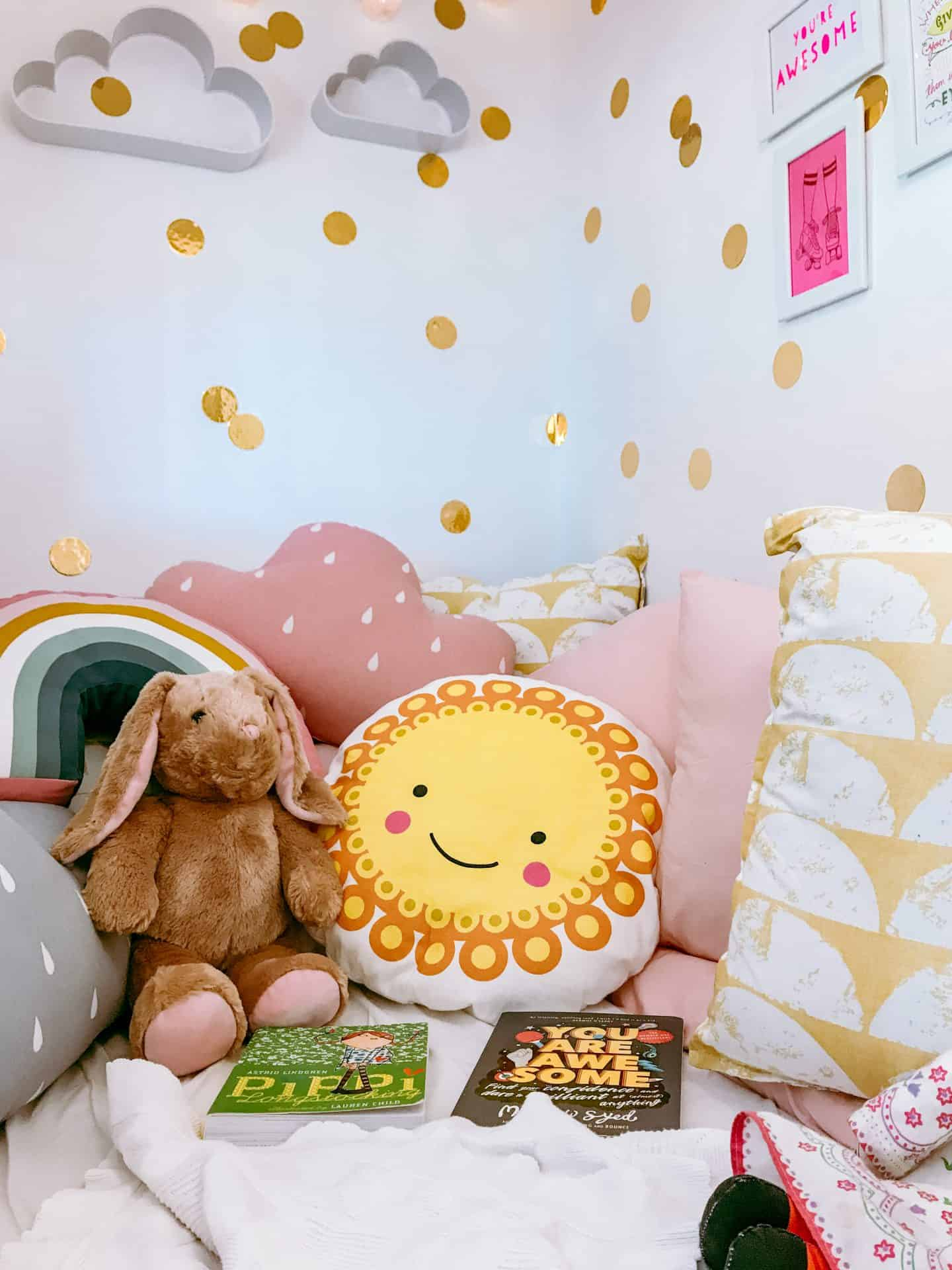 Kids' den with lots of pink and yellow cushions, books and cuddly toys, cloud shelves and gold wall decals