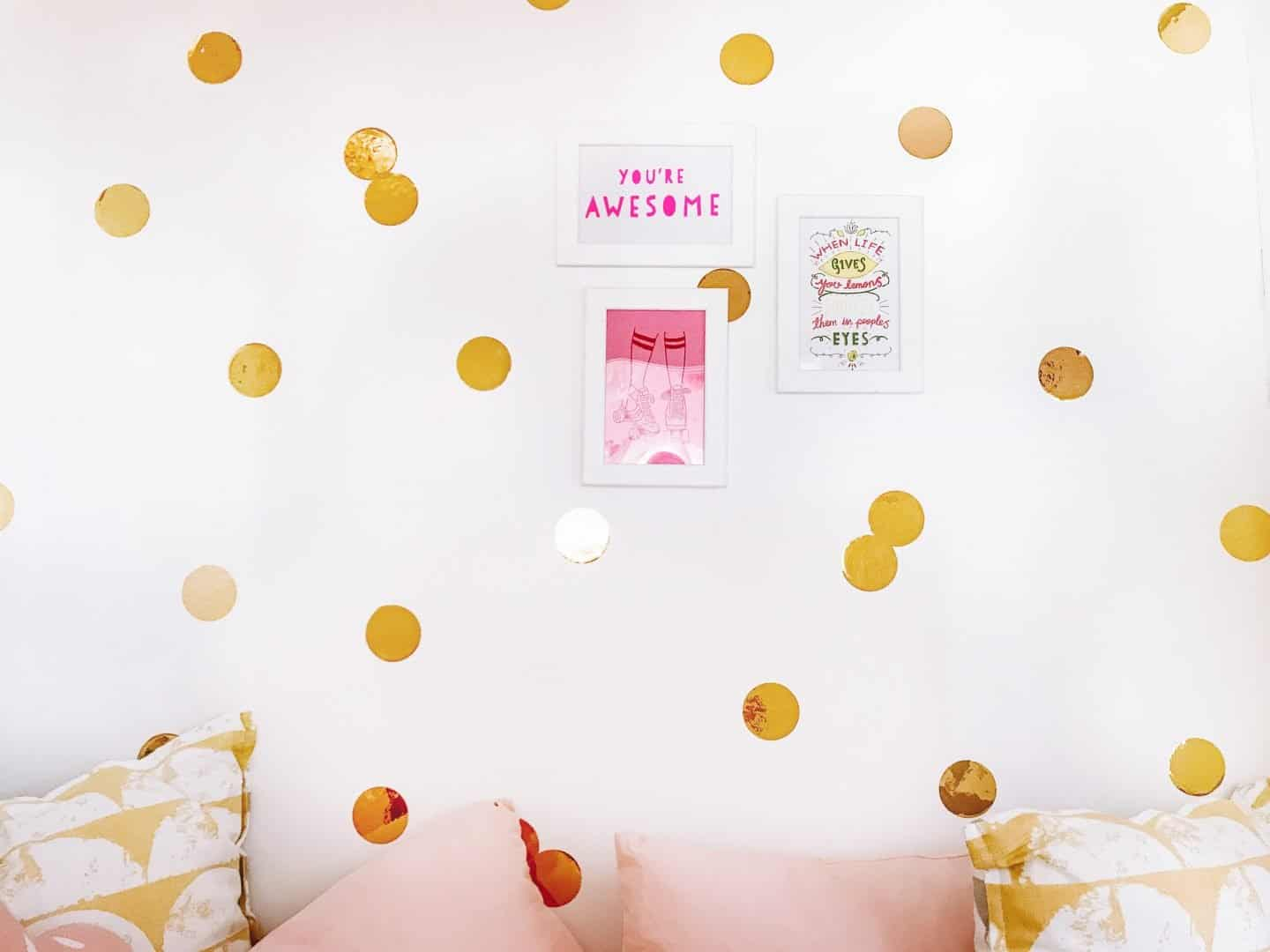 White wall with gold circular wall decals and white framed postcards